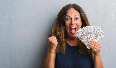 woman holding on to dollars with excited emotions